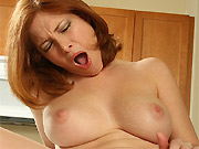 Busty redhead milf Ginger Blaze plays with dildo in kitchen