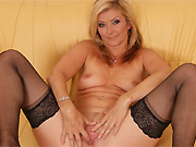 Horny mature blonde in black stockings poses on a sofa