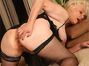 Busty mature blonde Zoe Zane poses in lingerie and stockings
