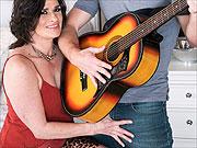 Smiling cougar seduces her guitar teacher