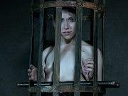 Lex Luthor blonde in purple is bound and caged in dark dungeon