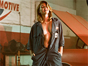 Sexy car mechanic stripping nude in the autobody shop