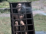 Wenona petite brunette is bound in metal cage outdoors and toyed