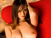 Brunette centerfold removes her bra and shows her big tits