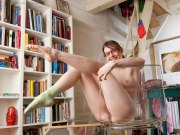 Girl with glasses posing nude in a glass chair