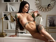 Tattooed babe with a nice rack poses nude at home